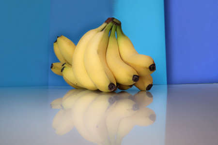 Hand of bananas front a blue background