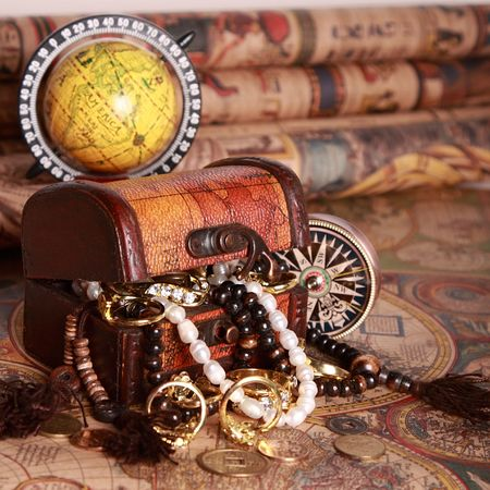 Antique chest with jewelry, compass, globe on vintage map photo