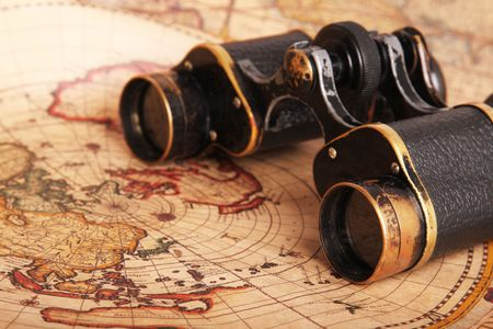 Old binoculars on antique map. Shallow depth of field photo