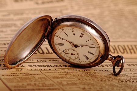 hands in pockets: Antique pocket watch on vintage newspaper