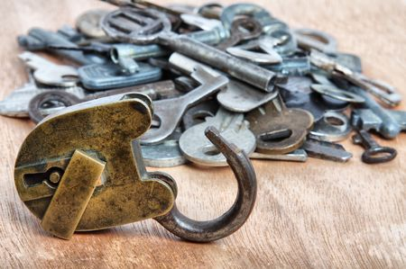 Old padlock and heap of keys on wooden background photo