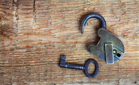 Old padlock and key on wooden background Stock Photo - 6906442