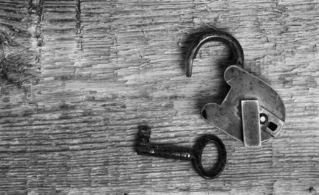 Old padlock and key on wooden background (black and white) photo
