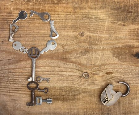 Old padlock and keys on wooden background photo