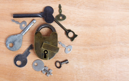 Old padlock and keys on wooden background