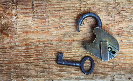Old padlock and key on wooden background  photo