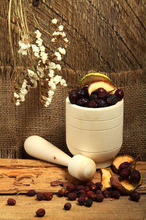 Wooden mortar with dog rose and dried apples photo