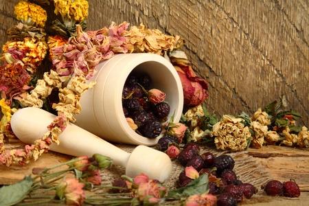 flores secas: Bodegón con mortero, rose hips y flores secas Foto de archivo