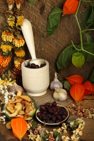 Autumn still-life with mortar, dried fruits and dry flowers  photo