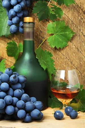 Still life with bottle, glass of cognac and bunch of grapes photo