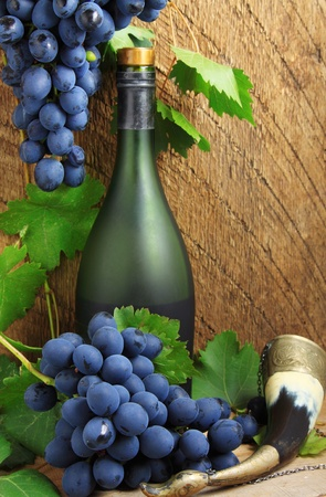 Still life - bottle, drinking horn and bunch of grapes Stock Photo