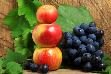 Three apples and bunch of grapes on wooden background photo