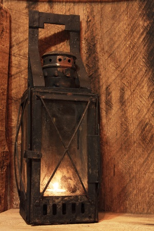 kerosene lamp: Old lamp with lighted candle on wooden background