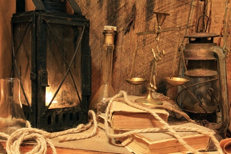 attic: Still life - old lamps, books and balance on wooden background