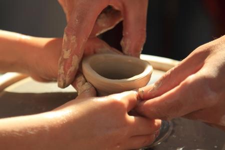 alfarero: Manos Potters dirigido las manos del niño, para ayudar a trabajar con la cerámica