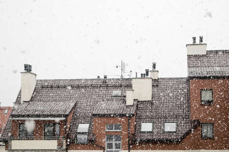 Snow white, large flakes of falling snow, view of the roof of the building with mounted antennas and ventilation pipes against the gray sky Imagens
