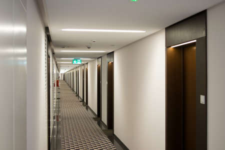 View of the long corridor in the hotel, lots of doors on both sides.