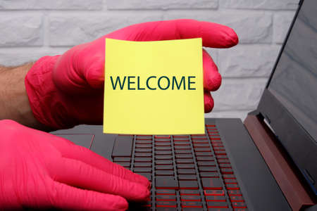 The word welcome on yellow paper in the hand with a red glove