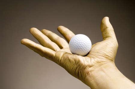 Golden hand holding golf ball Stock Photo - 3192965