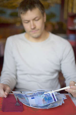 Man using chopsticks to pick up banknotes from a plate LANG_EVOIMAGES