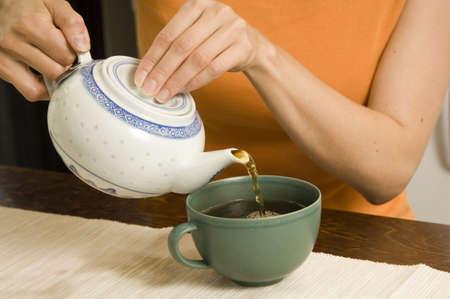 Woman pouring tea into teacup