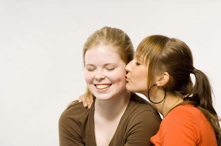 Teenage girl giving her friend a peck on the cheek