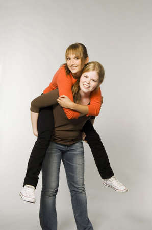 Teenage girl carrying friend on her back