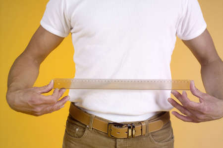 Man measuring his stomach with a ruler