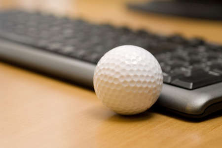 beside: Golf ball beside computer keyboard LANG_EVOIMAGES
