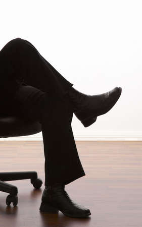 Legs of a business person sitting on an office chair Stock Photo - 3193033