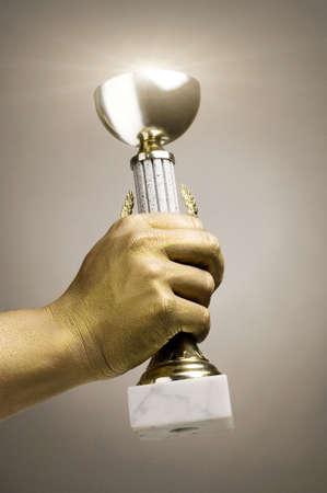 Golden hand holding trophy LANG_EVOIMAGES