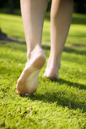 Woman walking barefoot on the grass LANG_EVOIMAGES