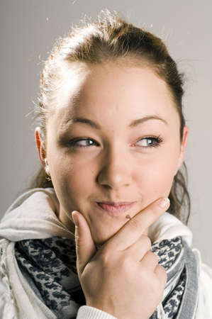 Teenage girl touching her chin while thinking