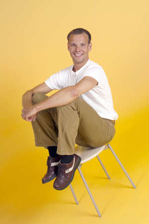 Man smiling at the camera while sitting on a stool Stock Photo - 3193082