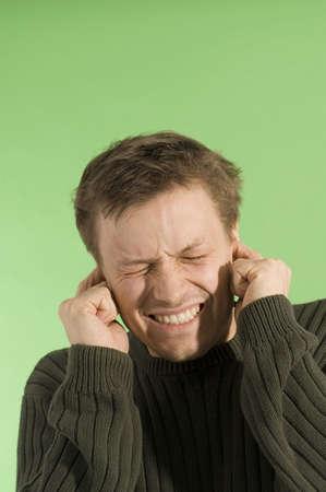 eyes closing: Man closing his eyes while covering his ears