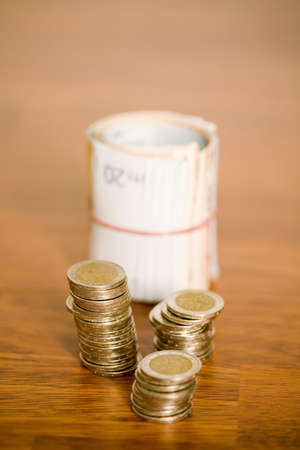 Stacked Euro coins and roll of banknotes Stock Photo - 3193233