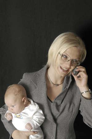 madre trabajadora: Trabajo madre hablando por el m�vil y con su beb�  LANG_EVOIMAGES
