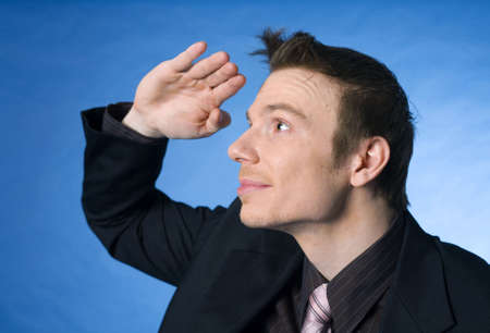 Businessman shielding his eyes looking into the distance Stock Photo - 3193311