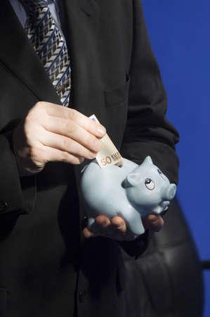 Businessman putting money into piggy bank