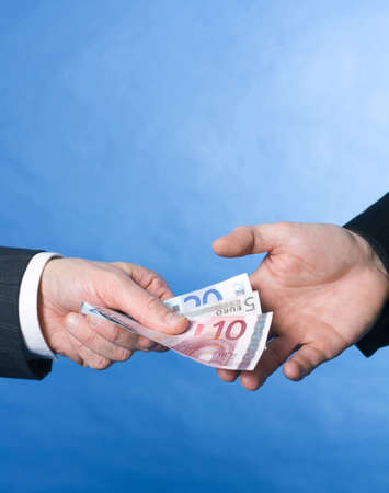 bribing: Businessman bribing another businessman with a bundle of cash LANG_EVOIMAGES