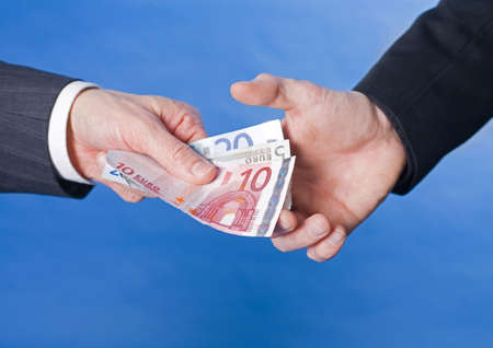 paying: Businessman bribing another businessman with a bundle of cash LANG_EVOIMAGES