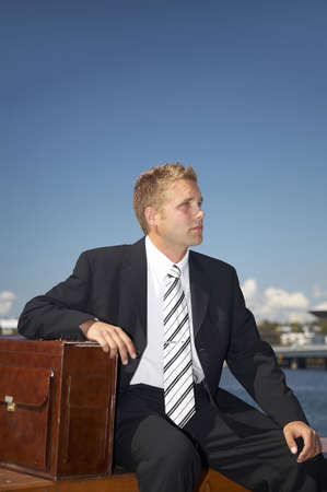 Businessman sitting outdoors with arm on briefcase Stock Photo - 3193374