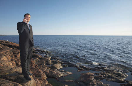 Businessman standing by the seaside talking on the mobile Stock Photo - 3193399