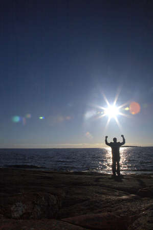visualizing: Businessman standing on the rocks with arms raised enjoying sunrise LANG_EVOIMAGES