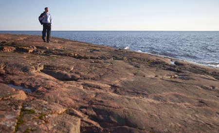 Businessman walking on the rocks enjoying sunlight Stock Photo - 3193418