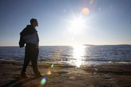 Businessman walking on the rocks enjoying sunlight