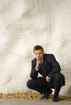 Businessman squatting in front of the camera Stock Photo - 3193423