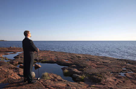 Businessman standing on the rocks holding a golf club Stock Photo - 3193435
