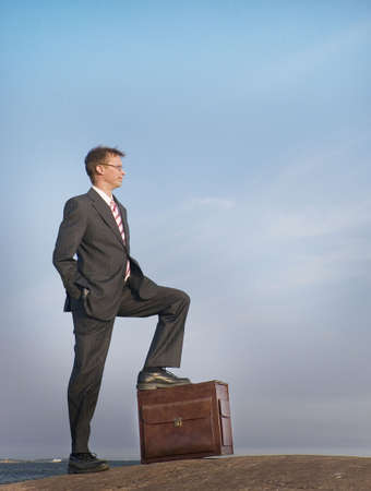 stepping: Businessman standing with his leg stepping on his briefcase