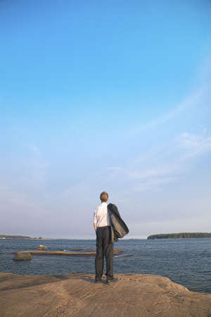 Businessman holding coat while enjoying the sea view Stock Photo - 3193438